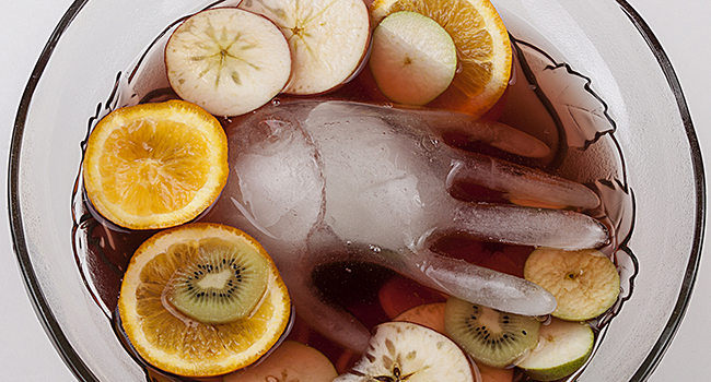 Ice shaped as hand in punch bowl.